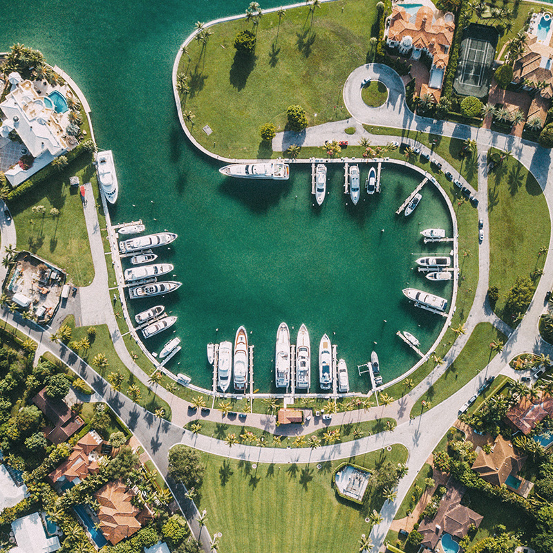 Top aerial view of a private boat marina and luxury homes.